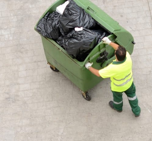 Man from city service pulling garbage bin